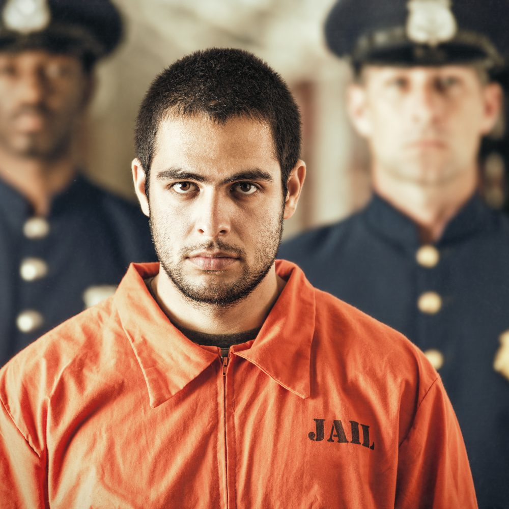 Portrait of a young male prison inmate in an orange jump suit stares at the viewer with an intimidating glare while two correctional officers stand guard in the background.